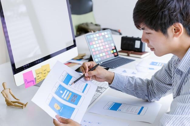 Кадр из креативного ux-дизайнера пользовательского интерфейса, разрабатывающего мобильное приложение для программирования и кодирования на основе макета прототипа и каркаса. концепция рабочего места разработчика мобильных приложений.
