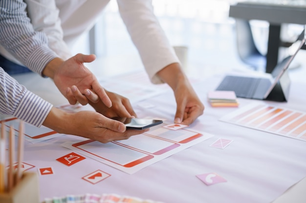 モバイルアプリ画面のワイヤーフレームワークフローについて話し合うクリエイティブuxデザイナーチーム。