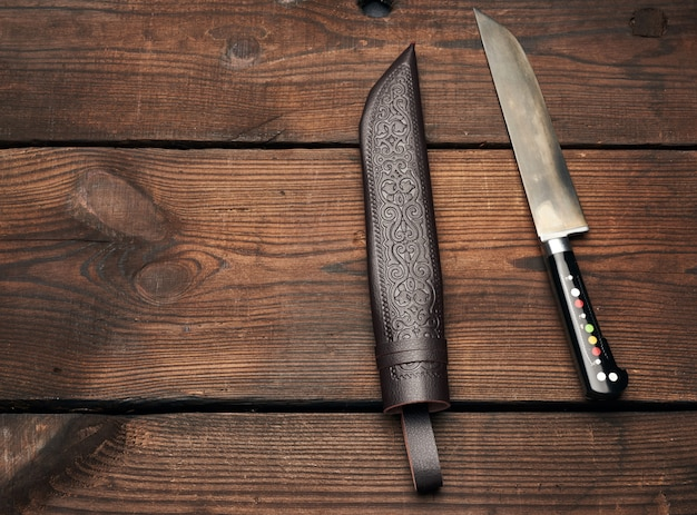 Uyghur uzbek traditional universal sharp knife with a black handle on a brown wooden background