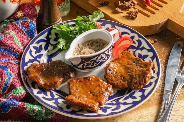 Узбекское блюдо хавас. сочные медальоны из говяжьей вырезки со свежими помидорами, зеленью и грибным соусом.