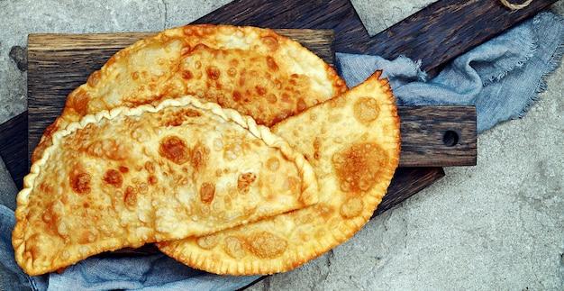 Узбекская восточно-татарская кухня, чебурек с мясом и сыром сулугуни и зеленью на деревянной доске.