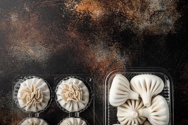 Узбекские манты. манты или пельмени с манти, популярный узбекско-азиатский набор блюд, в пластиковом подносе, на старом темном деревенском фоне, плоская планировка, вид сверху, с местом для текста
