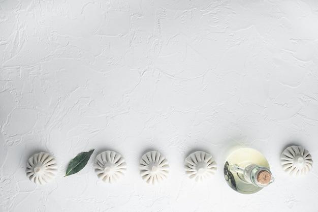 ウズベキスタンマンティ。マンティまたはマンティ餃子、人気のウズベキスタン料理セット、白い石の表面、上面図フラットレイ