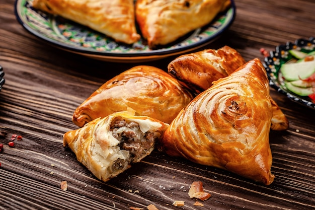 Uzbek national oriental cuisine. samsa with meat on a wooden background. background image. copy space.