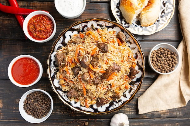 Узбекский плов - рисовое блюдо, приготовленное из говядины, тушенное с жареным луком, чесноком и морковью, рисом, сухофруктами, чесноком и тмином.