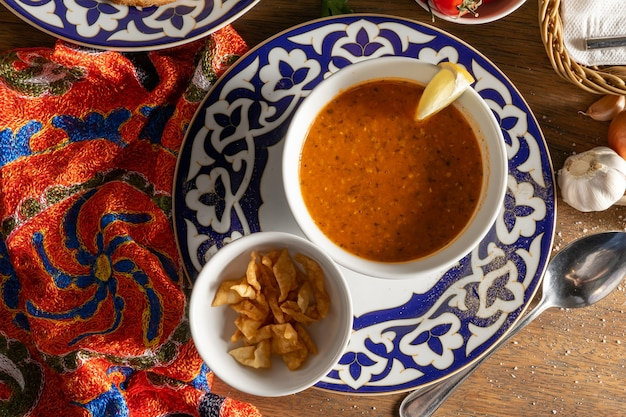 レンズ豆、玉ねぎ、ミント、トマトペーストから作られたウズベキスタンのスープ。レモンとピタフライのパンを添えて