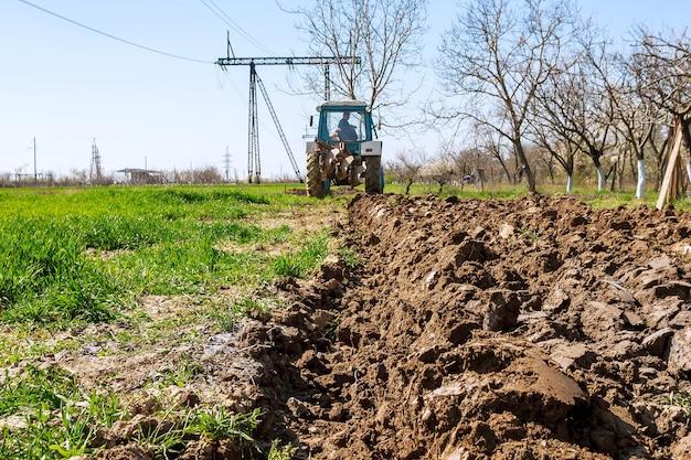 Uzhhorod, 우크라이나, 2020 년 4 월 8 일 : 파종을 위해 쟁기로 땅을 준비하는 파란 트랙터의 농부