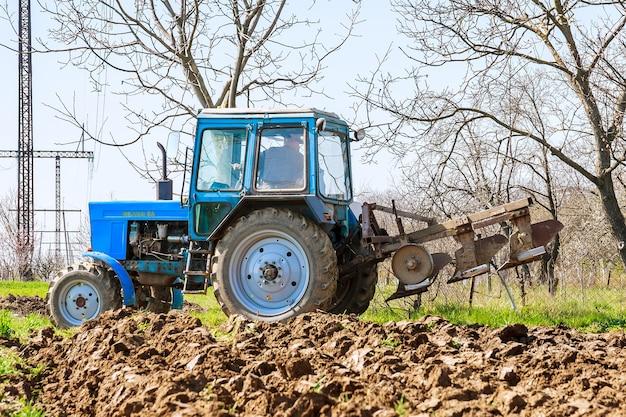 Uzhhorod, 우크라이나, 2020년 4월 8일: 파종을 위해 쟁기로 땅을 준비하는 파란색 트랙터를 입은 농부