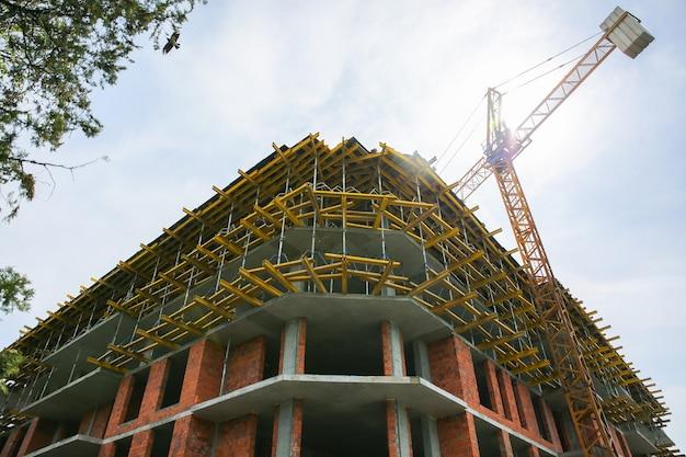 Uzhhorod, ukraine - april 14, 2019: house building in process. yellow crane. city development.