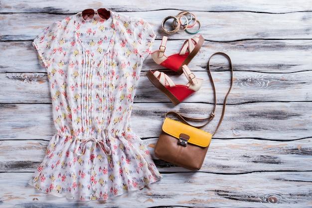 Vネックブラウスとウェッジサンダル。バッグ付きの赤いウェッジシューズ。女の子の快適な夏の服装。ブティックでの特別価格。