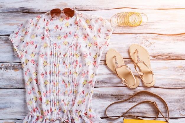 V-neck blouse with bright pattern. blouse, sandals and sunglasses. clothes on white wooden showcase. brand new clothing for women.