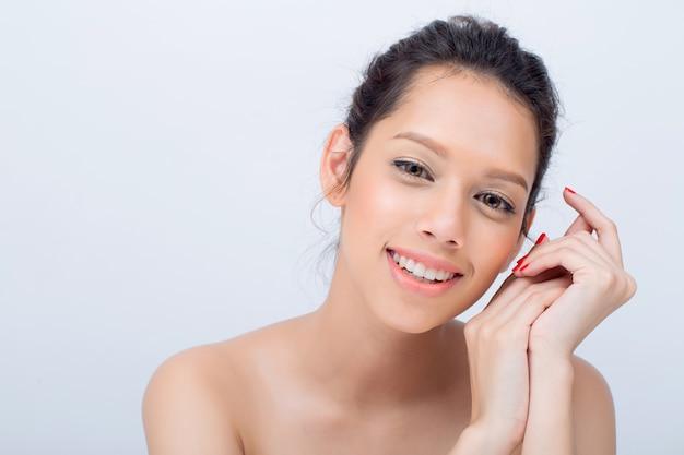 Красота v-shape лицо азиатской молодой женщины фотомодель с естественным макияжем коснуться ее лицо на белом фоне
