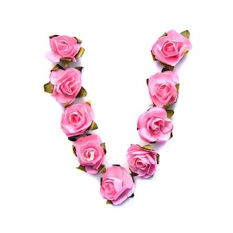Буква v английского алфавита из розовых роз на белой поверхности
