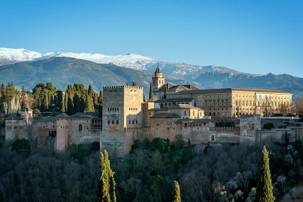 Вид на дворец альгамбра и карла v с национальным парком сьерра-невада на заднем плане, в городе гранада, андалусия, испания