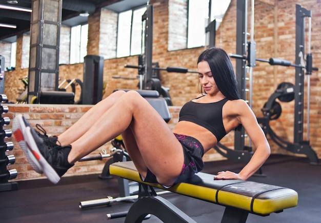 ポーティな女の子のコンセプトでワークアウト、ジムでvアップ腹筋トレーニングを行う