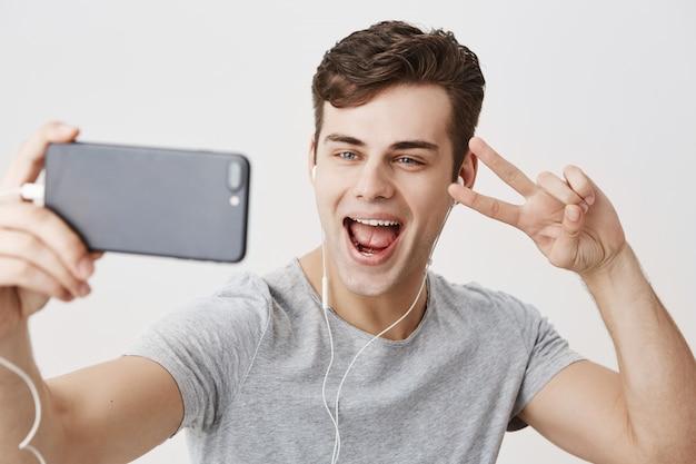 白いイヤホンを着ている若いハンサムな白人男性、携帯電話を持っている、ビデオ電話をかける、自分撮りのためにポーズする、広く笑って、vサインを示す。現代のコミュニケーションとテクノロジー。