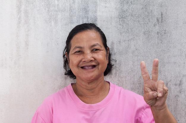 Улыбаясь портрет тайской женщины и показывая знак v