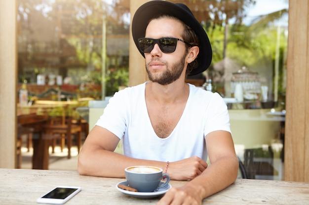 トレンディなサングラスと白いvネックシャツのファッショナブルな若い男が歩道のカフェテリアで休憩をとり、カプチーノを飲む