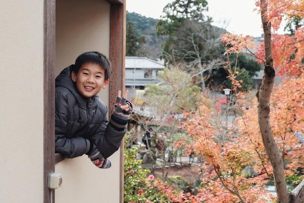 Счастливый азиатский мальчик, улыбаясь с жестом руки знак v япония осень, предподростковый путешествие
