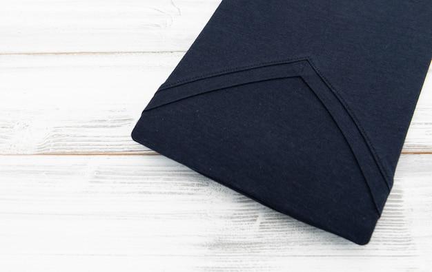白い木製の背景に新しい黒vネックシャツ