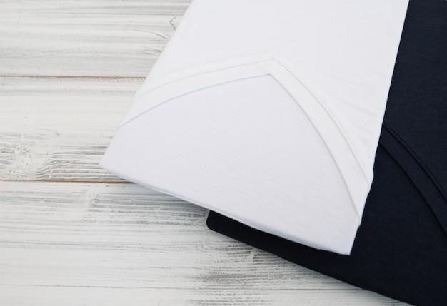 白い木製の背景に新しい黒と白のvネックシャツ