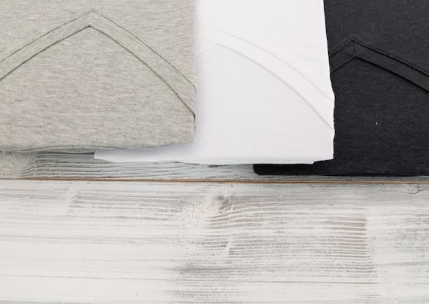 白い木製の背景に新しい黒、白とグレーのvネックシャツ