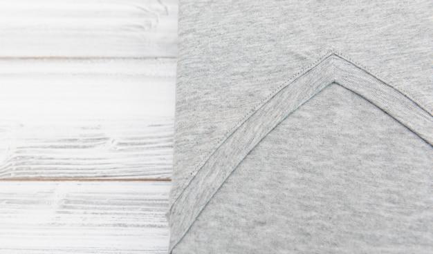 白い木製の背景に新しいグレーvネックシャツ