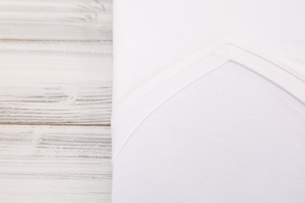 白い木製の背景に新しいvネックシャツ