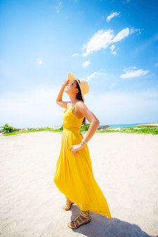 Красивая азиатская молодая женщина нося желтое платье ослабляя на пляже vacaiton лета