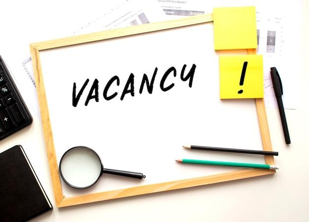 Vacancyのテキストは白いオフィスボードに書かれています。事務用品を備えた作業台。ビジネスと財務の概念。