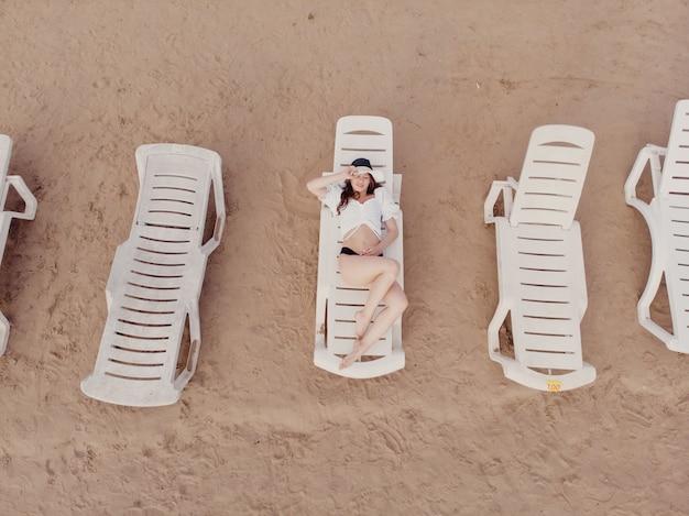 휴가와 모험. 해변, 해변 의자 및 휴식 소녀에서 무인 항공기에서 상위 뷰