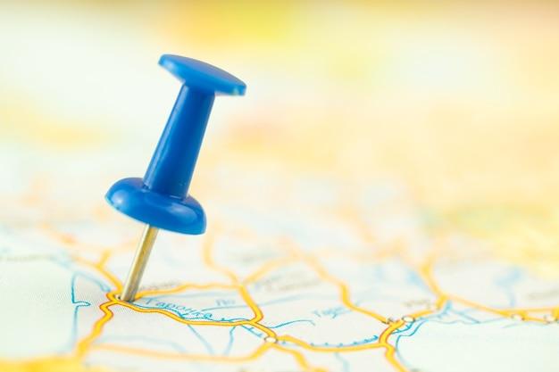 Концепция отпуска и путешествий, синяя канцелярская кнопка на карте, пункт назначения, фото с выборочным фокусом