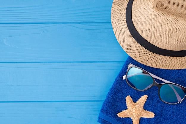 해변 개념에서 휴가입니다. 오버헤드 뷰 위의 클로즈업 사진 위에 타월 선글라스 불가사리와 카피스페이스가 있는 푸른 나무 배경에 격리된 태양 모자