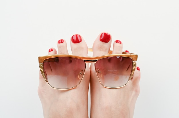Vacation concept on the beach. feet in glasses on a white space close-up