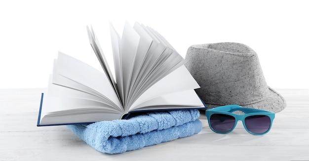 Концепция отпуска. книга, полотенце и шляпа на белом деревянном столе