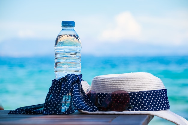 Vacation concept. essentials on the sea beach. bottle of drinking water,summer white hat