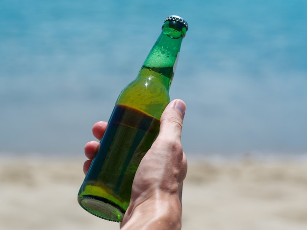 Vacation concept. male hand holding new bottle of beer on the ocean beach.