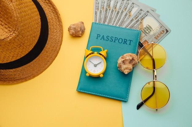 休暇の概念。イエローブルーの表面にパスポート、サングラス、帽子、シェルを備えた最小限のシンプルなフラットレイ。観光の必需品