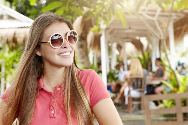 Vacation concept. outdoor shot of pretty girl in trendy shades and polo shirt smiling joyfully while relaxing at cafe at health resort, spending holidays in hot exotic country.