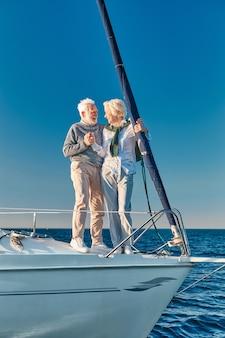 手をつないでお互いを見ながら恋に幸せな年配のカップルの完全な長さの休暇