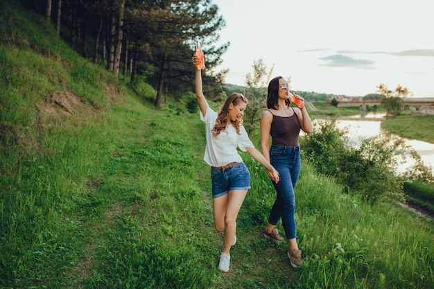 Vacation and happiness concept, two girls have fun, drink cocktail from the bottle, summer fun, at sunset, positive facial expression, outdoor