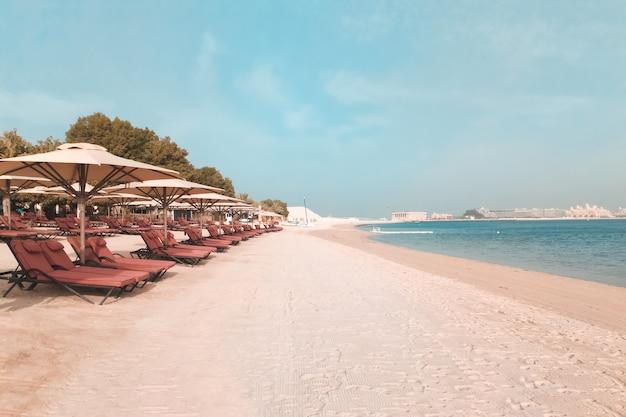 休暇の休日のビーチの背景。ドバイのアラビア湾岸にあるサンベッドとサンシェードのあるビーチ。