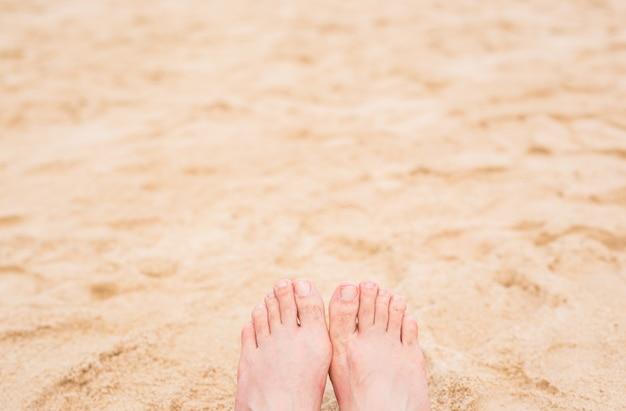休暇の休日。日当たりの良い夏の日にビーチでリラックスした女の子の女性の足のクローズアップ。