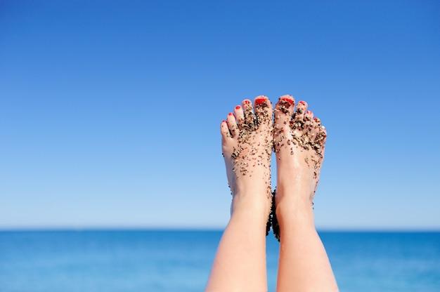 휴가 휴가. 해변에서 편안한 여자의 여자 발 근접 촬영