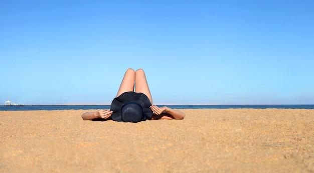 휴가 휴가 태양을 즐기는 일광욕용 침대가 있는 모래 해변에서 모자를 쓰고 있는 여성
