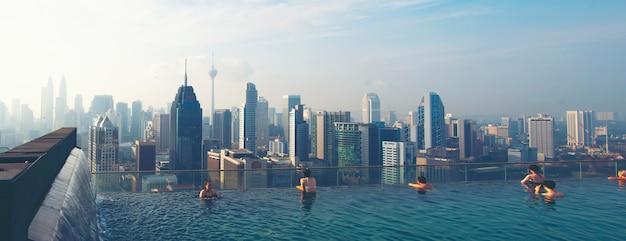 Отдых в куала-лумпуре. молодая женщина любит купаться в бассейне на крыше с прекрасным видом на город
