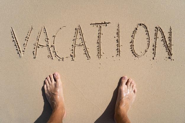 Отпуск надпись на летнем песчаном пляже с мужскими ногами. концепция отдыха и приключений.