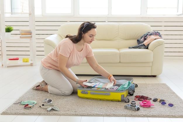 休暇、旅行、休日のコンセプト-床に服を集める女性。