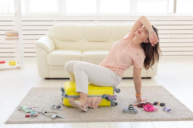 Концепция отпуска, путешествия и праздников - женщина танцует, пока она собирает одежду для путешествия