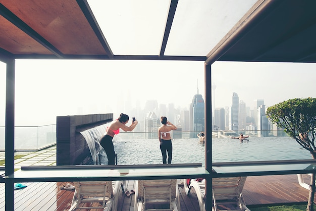Vacation in kuala-lumpur. young woman enjoy swimming in roof top pool with beautiful city view